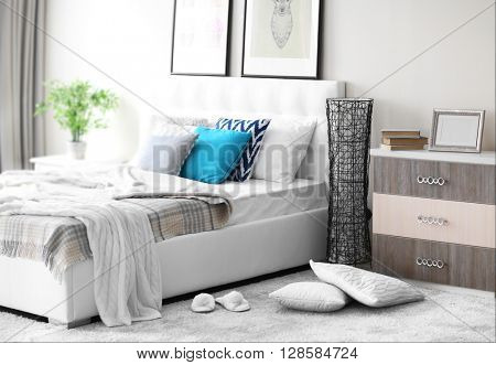 Bedroom interior in light tones with white furniture and pictures on the wall