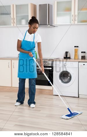 Young Female Janitor Mopping Hardwood Floor In Kitchen
