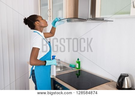 Young African Woman Cleaning Cooker Hood With Rag In Kitchen