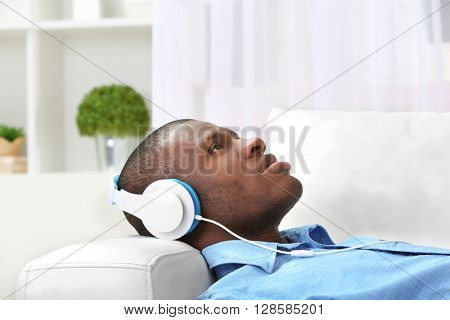 Handsome African American man with headphones lying on sofa in room