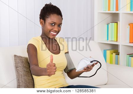 Happy Young African Woman Sitting On Sofa Measuring Blood Pressure At Home