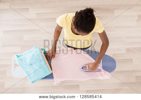 High Angle View Of African Woman Ironing Clothes On Ironing Board