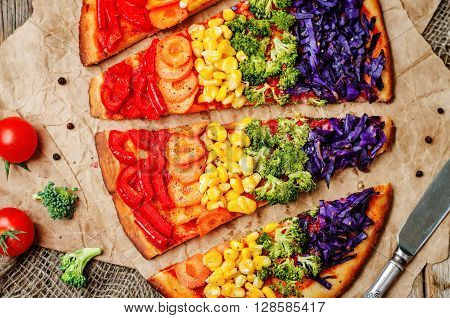 rainbow vegan pizza on a dark wood background