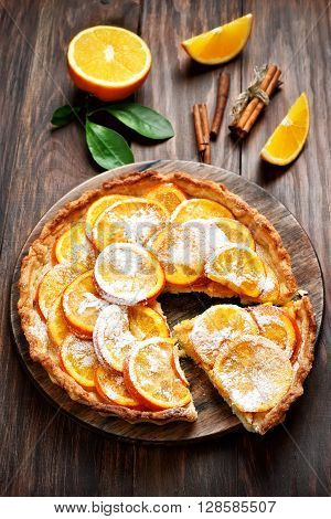 Fruit tart with orange caramelized slices on wooden table