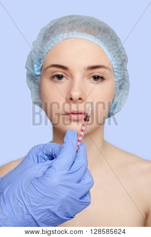 Attractive young woman gets cosmetic injection. Doctors hands making an injection in face close-up. syringe in focus out of focus pattern on the background