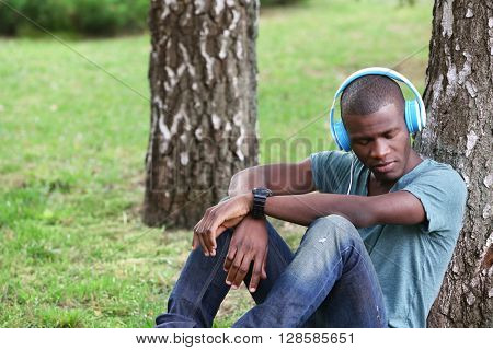 Handsome African American man with headphones sitting in park