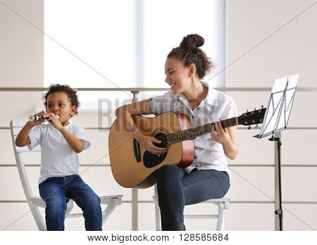Young girl and little boy playing on music instruments