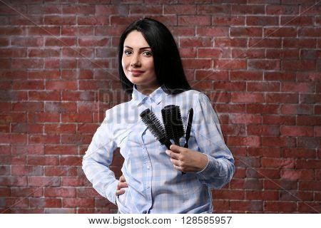 Beautiful woman with combs on brick wall background