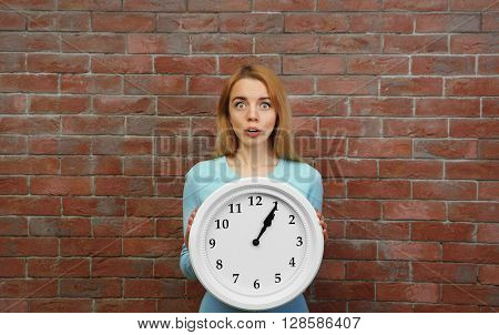 Young beautiful woman holding clock against brick wall background
