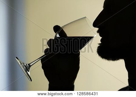 Silhouette of man tasting red wine, close-up