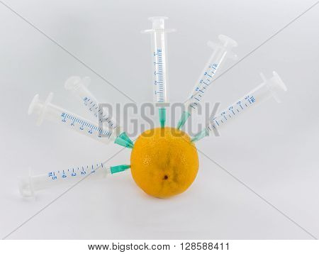 Lemon in a medical syringe on a gray background. Introduction to fruit chemicals nitrates.
