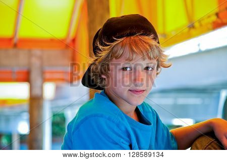 Portrait of cute kid with long curly hair looking happy.