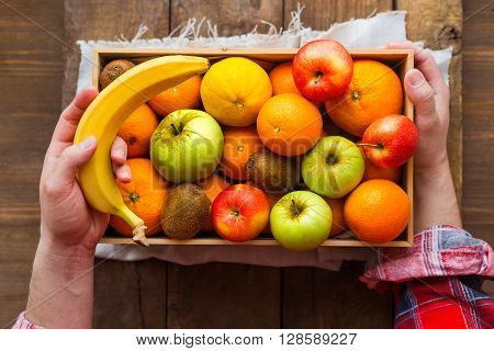 Man in tartan plaid shirt holds a box full of fresh fruits and a banana. Fruit harvest - apples oranges lemon kiwi banana. Rustic wooden table.