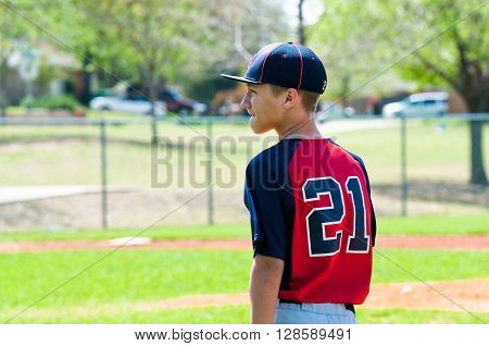 Teenage baseball boy close up with copy space during game.