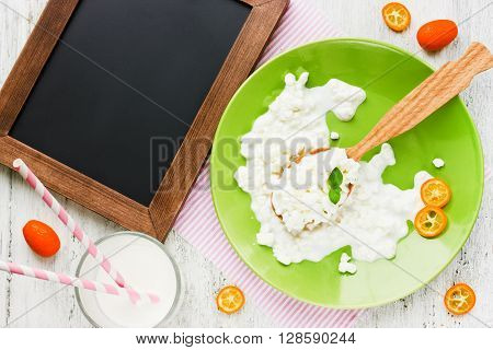 Dairy products (fresh natural cottage cheese yogurt) and sliced kumquats on a white table. Cooking concept of healthy breakfast. Top view and blank space for text on the chalkboard
