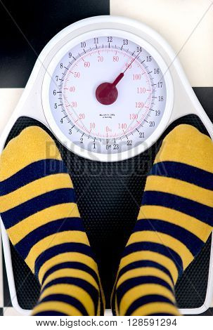 bathroom weighing scales and yellow striped socks on black and white flooring