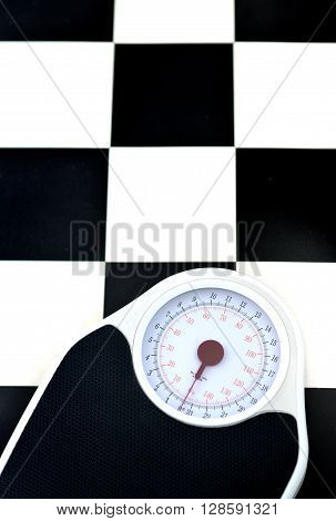 bathroom weighing scales on black and white flooring