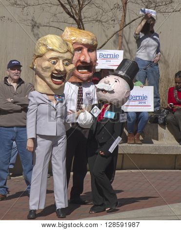 Asheville, North Carolina, USA - February 28, 2016: Humorous effigies of Hillary Clinton Donald Trump and Mr. Monopoly stand close together holding bags of money with Bernie Sanders supporters with signs behind them at a Bernie Sanders campaign rally