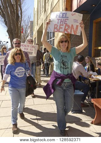 Asheville, North Carolina, USA - February 28, 2016: A crowd of Bernie Sanders rally supporters march holding a variety of signs about isuues like health care during a campaign rally on February 28 2016 in downtown Asheville NC