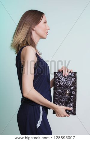 Elegant fashionable woman with leather handbag. Stylish girl on green holding black bag. Female fashion vogue. Studio. Side profile view.