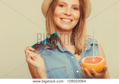 Happy glad woman tourist in straw hat holding sunglasses and grapefruit citrus fruit. Healthy diet food. Summer vacation holidays concept. Instagram filtered.