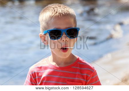Portrait of little young boy kid child in sunglasses licking lollipop at sea. Summer holidays vacation.