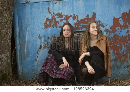 Teen girls sitting on a background of old iron wall.