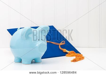 Blue piggy bank and graduation cap. Conveys the concept of the cost of higher education.