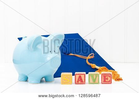 Blue piggy bank and graduation cap. Conveys the concept of saving early for education.