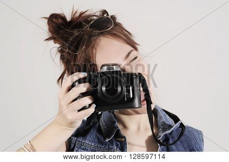 Funny young and trendy hipster girl looking into photo camera with emotions