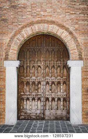 Arched entrance of a medieval palace with carved wooden door.