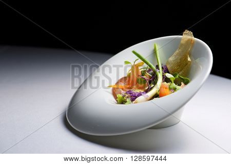 Closeup of a white bowl of salad.