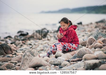 Young school girl playing at the beach with rocks, still life photo