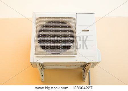 Air compressor white color with concrete wall background.