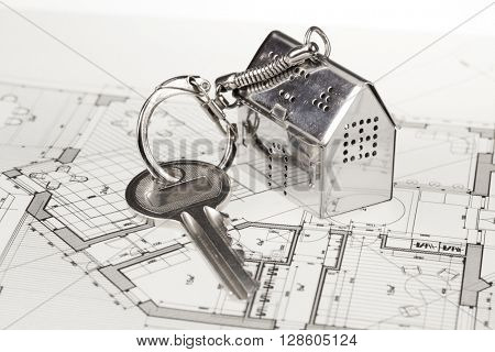 key with keychain in the form of a silver-colored house on a background of architectural drawing