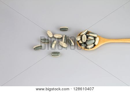The Herbal Supplement vitamin pills or tablets in wooden spoon