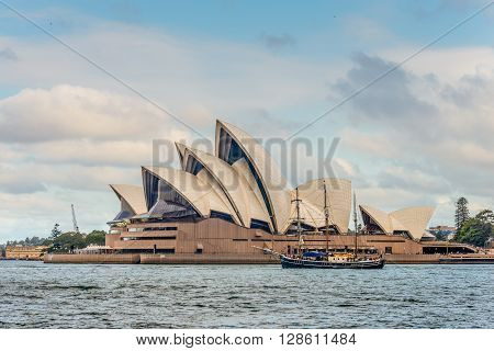 Sydney Australia - November 10 2014: A view of the iconic Sydney Opera and Tall Ship sailing in the Sydney Harbour Sydney New South Wales Australia
