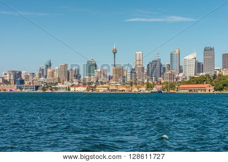 Sydney Australia - November 9 2014: Water front panorama of Sydney Central Business District office buildings showing centrepoint tower Sydney New South Wales Australia. The Garden Island dockyard in the foreground.