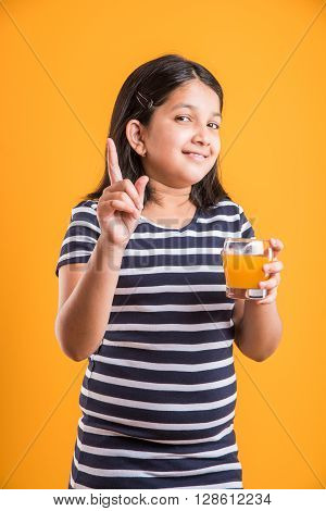 portrait of indian small girl drinking mango juice or fruit juice in a glass, asian girl and a glass of juice, indian small girl holding a glass of mango juice or orange juice on colorful background