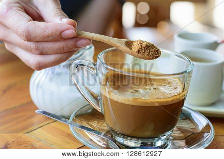 Morning cup of hot coffee with sugar on table
