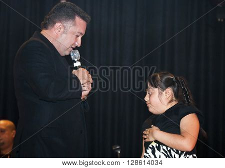 BRONX NEW YORK - MARCH 17: Samuel Hernandez performs with a down syndrome child during a Christian concert for Realizing Possibilities ministry. Taken March 17 2012 in New York.