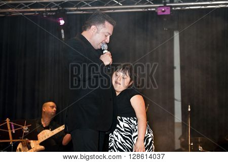 BRONX NEW YORK - MARCH 17: Samuel Hernandez performs while holding a down syndrome child during a Christian concert for Realizing Possibilities ministry. Taken March 17 2012 in New York.