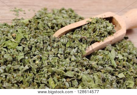 Heap of dried marjoram with wooden spoon on wooden background seasoning for cooking concept for healthy nutrition