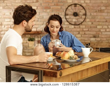 Young couple having breakfast in the morning at home.