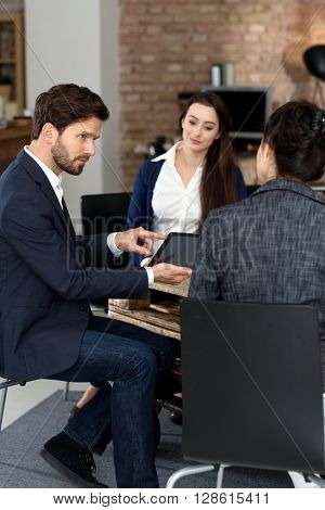 Businesspeople working in startup office, using tablet.