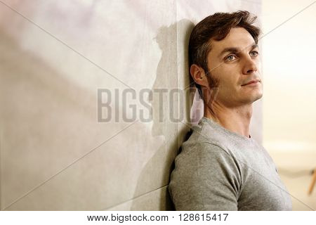 Portrait of daydreaming man leaning against wall, casting a shadow.
