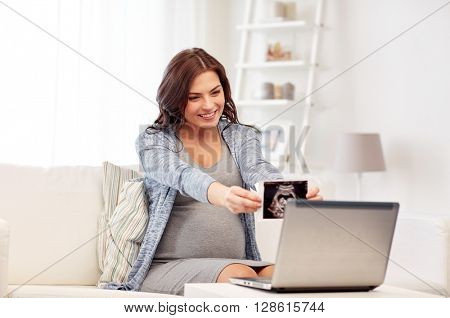 pregnancy, motherhood, people and medicine concept - happy pregnant woman with laptop computer having video call and showing ultrasound image at home