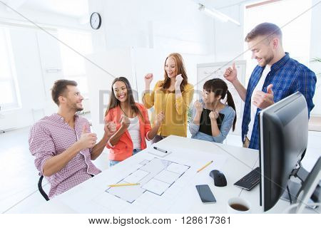 business, success, architecture, gesture and people concept - happy international creative architect team or students with blueprint celebrating triumph at office