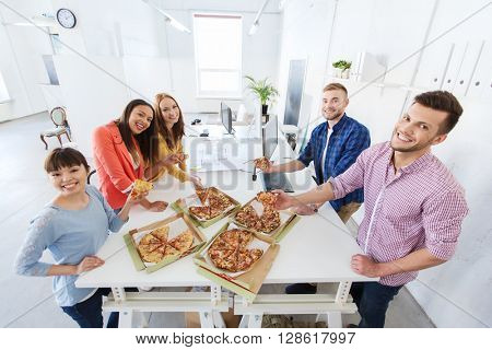 business, food, lunch and people concept - happy international business team eating pizza in office