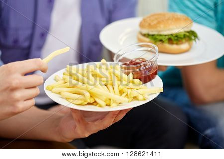 fast food, unhealthy eating, people and junk-food - close up of male hands with french fries, ketchup and hamburger on plates